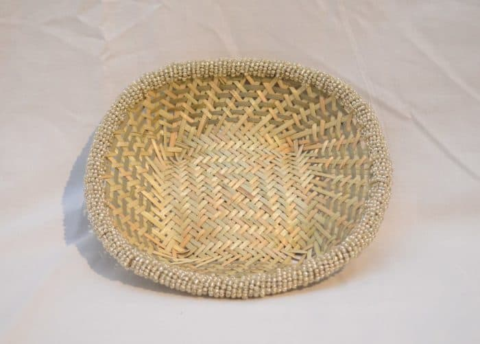 "Main product image from the top of a small woven basket from iraca with white beaded border, 9"" wide"