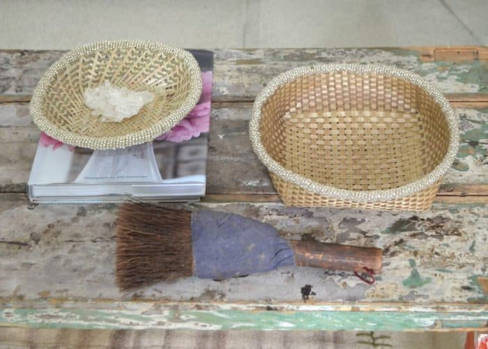 45 degree view picture of two small woven baskets made from iraca with white beaded border on shabby chic table next to a vintage decorative brush