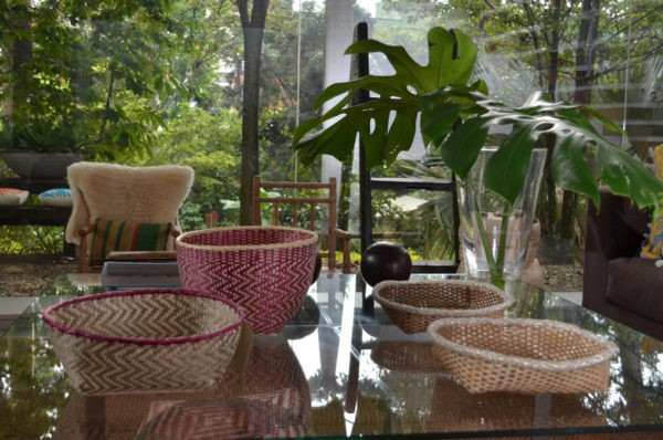 Picture of two small woven baskets made from paja tetera and two made from iraca and white beaded border sitting on a glass centerpiece table with a tropical setting background
