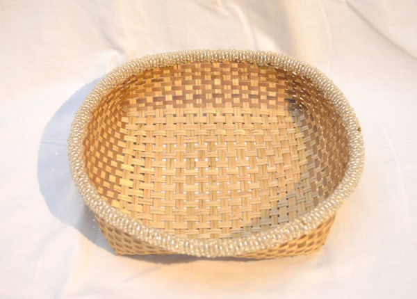 Main product image from the top of a small woven basket from iraca with white beaded border