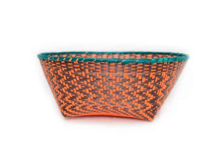 main product image of a small woven basket made from paja tetera natural fibers with border in aqua color, and orange/brown pattern
