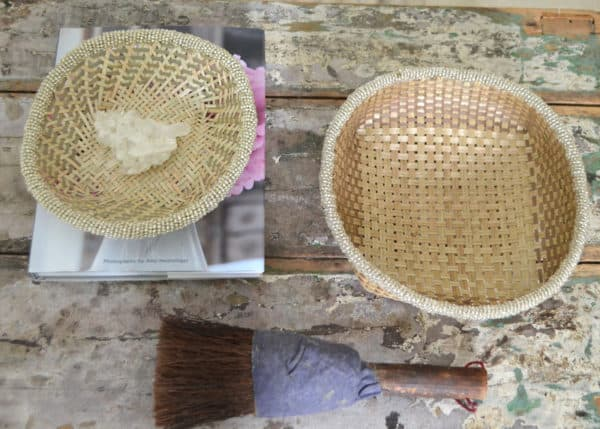 Top view picture of two small woven baskets made from iraca with white beaded border on shabby chic table next to a vintage decorative brush