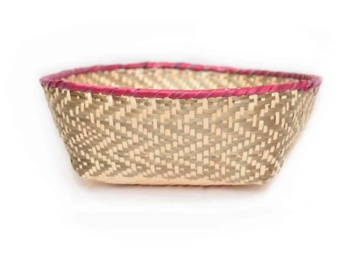 main product image of a small woven basket made from paja tetera natural fibers with border in pink and grey pattern