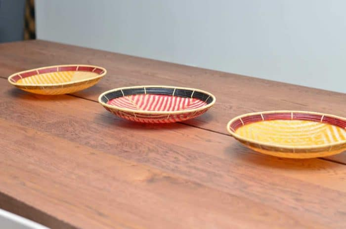 picture of three flat baskets to hang on wall (aka. balays) lined up on top of a wooden table