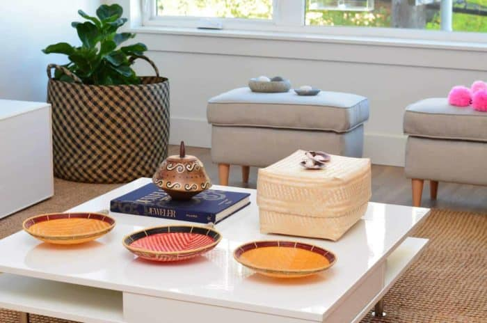 Picture of three flat baskets to hang on wall (aka. balays) and a white rectangular woven basket with lid made from paja tetera fibers on top of a white living room table with a extra large woven basket made from iraca fibers being used as a planter sitting in the baskground