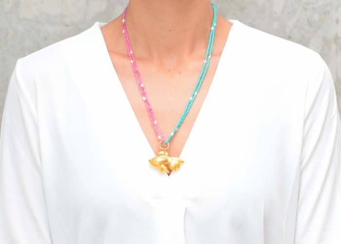 picture of a woman wearing a Turquoise and Pink Agate Necklace with Gold Fish Pendant and Tiny Pearls by Kiskadee Design