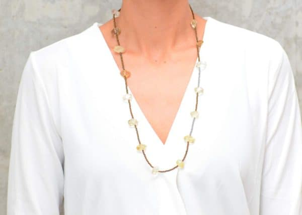 picture of a woman wearing a Long Dainty Raw Citrine Quartz Necklace by Kiskadee Design