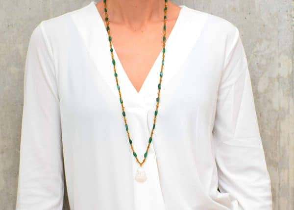 picture of a woman wearing a Long Raw Emerald Necklace with Mother of Pearl Buddha Pendant by Kiskadee Design