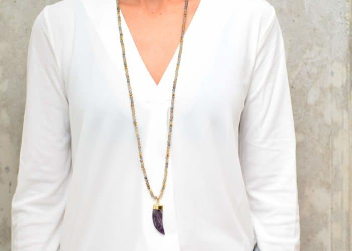 picture of a woman wearing a Long Labradorite Bead Necklace with Amethyst Pendant by Kiskadee Design