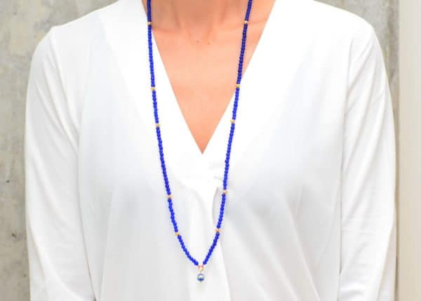 picture of a woman wearing a Blue Murano Bead Necklace with Enamel Charm and Gold-Filled Accent Beads by Kiskadee Design