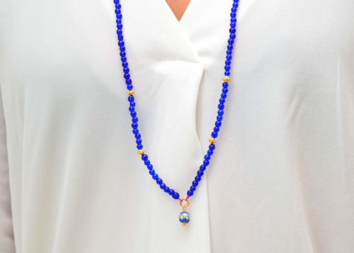 close up picture of a woman wearing a Blue Murano Bead Necklace with Enamel Charm and Gold-Filled Accent Beads by Kiskadee Design