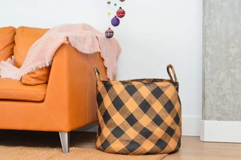 Picture of Tan Iraca Large Woven Basket with Black Stripes next to a leather sofa