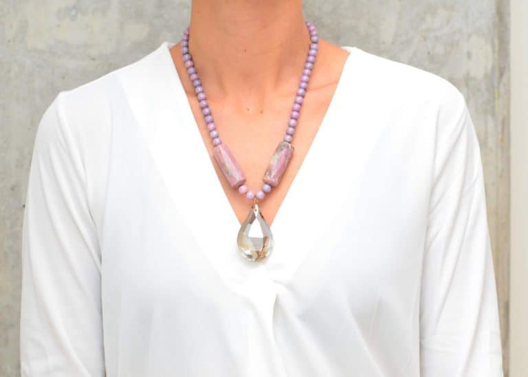 picture of a woman wearing a Lepidolite Necklace with tear-drop Grey Crystal Pendant by Kiskadee Design