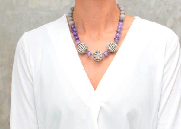 picture of a woman wearing an Amethyst Bead Necklace with Grey Agate and Crystal Accents by Kiskadee Design