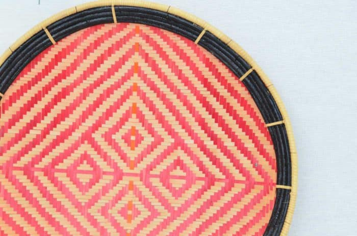 close up product image of the frame and pattern of a small flat basket to hang on wall (aka. Balay) with a Red and White pattern that resembles a Tiger Skin and Black Frame.