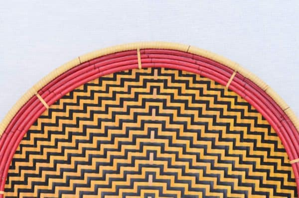 close up product image of the frame and pattern of a small flat basket (aka. Balay) with a Yellow and dark brown pattern that resembles a Spider Web and a red frame