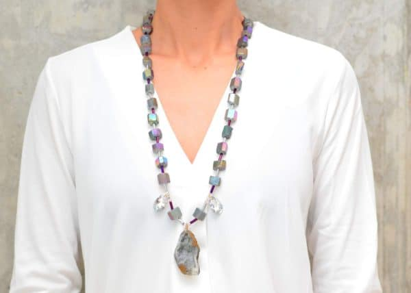 picture of a woman wearing a Peacock Ore Necklace with Crystals and Geode Pendant by Kiskadee Design