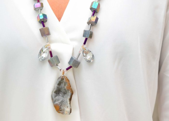 close up picture of a woman wearing a Peacock Ore Necklace with Crystals and Geode Pendant by Kiskadee Design