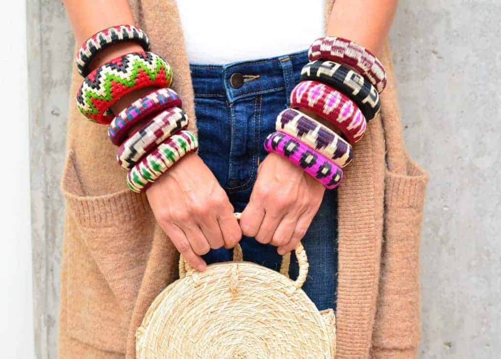 Picture of various colorful bangle bracelets made from werregue being worn by a woman on her arms while she holds an circle handbag made ofrom iraca