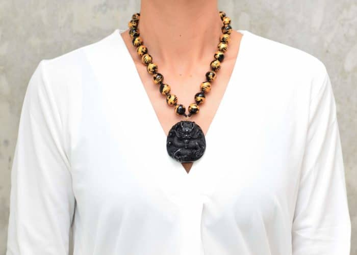 picture of a woman wearing a Hand Painted Onyx Bead Necklace with Hand Carved Dragon Pendant by Kiskadee Design