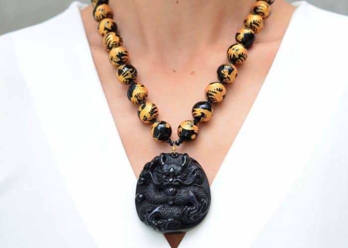 close up picture of a woman wearing a Hand Painted Onyx Bead Necklace with Hand Carved Dragon Pendant by Kiskadee Design