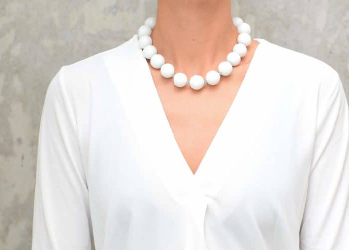 picture of a woman wearing a White Faceted Jasper Necklace by Kiskadee Design