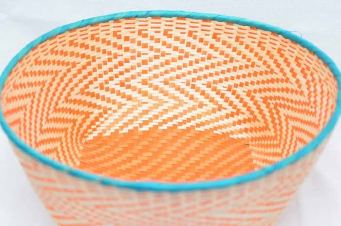 Main product image from the top of a small woven basket with aqua colored border and orange pattern walls