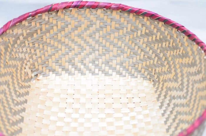 Main product image from the top of a small woven basket with border in pink and grey pattern walls