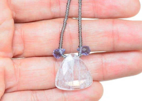 close up picture of a Quartz Pendant Necklace with Glass Beads and Faceted Amethyst Accent Drops on being held on a hand by Kiskadee Design