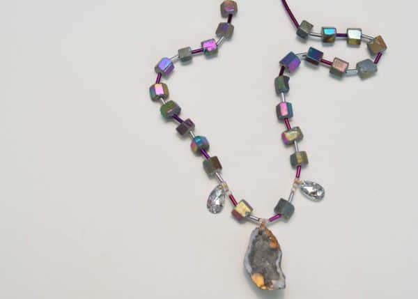 second close up picture of a Peacock Ore Necklace with Crystals and Geode Pendant on white background by Kiskadee Design