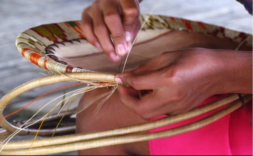 Woman weaving a werregue piece