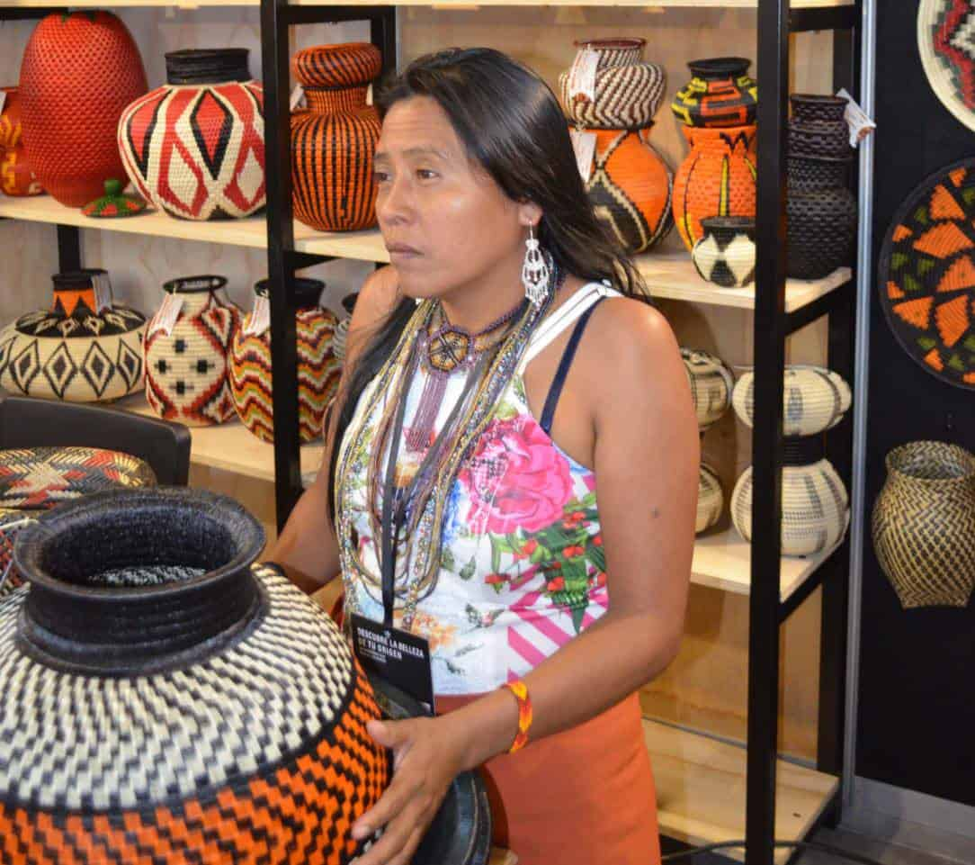Picture of a Wounaan woman displaying various decorative bowls and vases made from Werregue fibers
