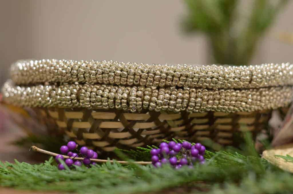 Close up view of two bread baskets made of iraca and brown metallic beaded border next to purple plant seeds and green pine tree leaves