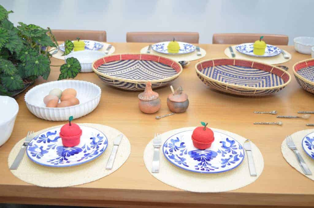 Picture of hand painted dinner plates, condiments serving clay chickens and Small Woven Baskets in Iraca on a weekend lunch table setting