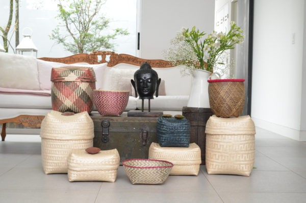 Picture of various woven baskets sitting next to the head of a Buddha statue in a living room setting