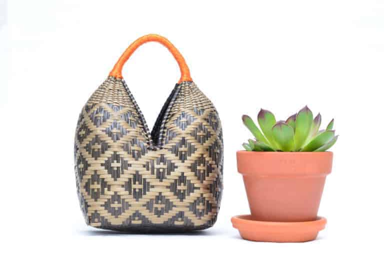 Main product image of a small dos tetas basket in brown shrimp eyes pattern with golden orange handles sitting next to succulent in a planter