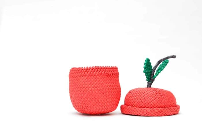 picture of a tiny apple shaped basket woven in red iraca with its lying on the side