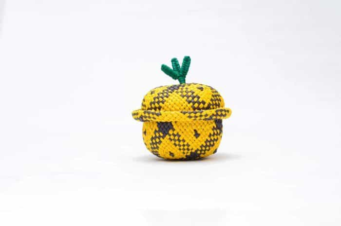 product picture of a small pineapple shaped basket woven from iraca fibers with its lid on