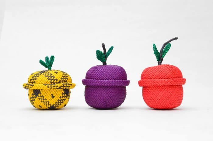 picture of three little woven baskets shaped in the form of a pineappple, a grape, and a red apple made from iraca fibers in sandona, colombia