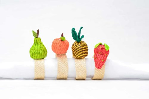 Picture of unique napkin rings with the following fruits woven from iraca: pear, mandarin, pineapple and strawberry