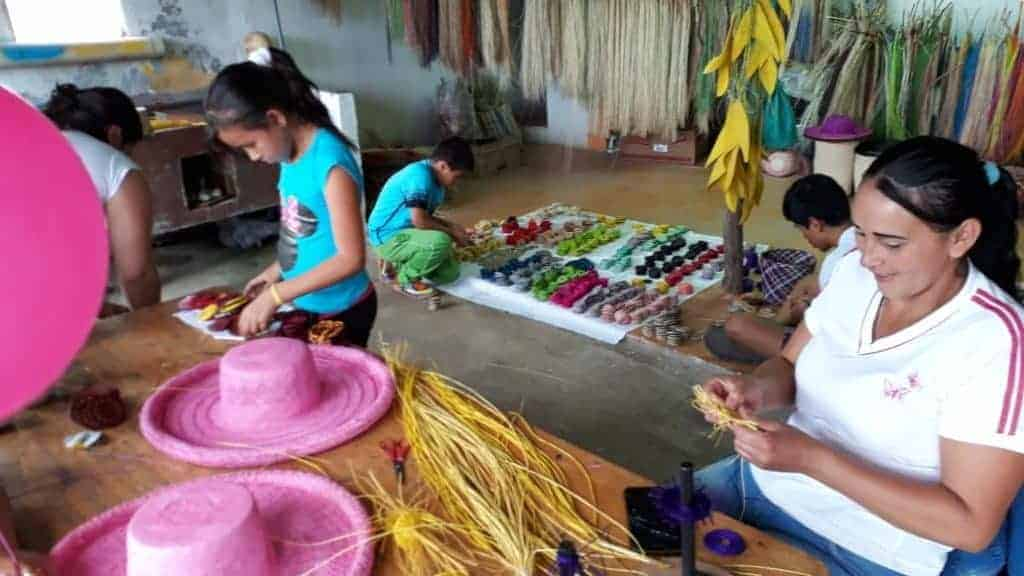 picture of sandoneñas weaving colorful crafts from iraca palm fibers in Colombia