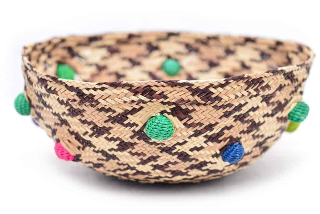 Picture of a small decorative bowl woven from iraca fibers with colorful accents