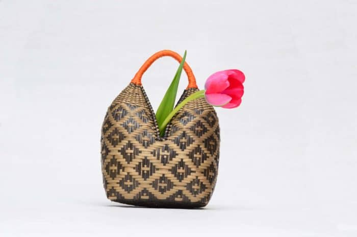 Picture of a Eperaara Siapidaara dos tetas basket hand woven in brown shrimp eyes pattern with golden orange handles holding a red tulip