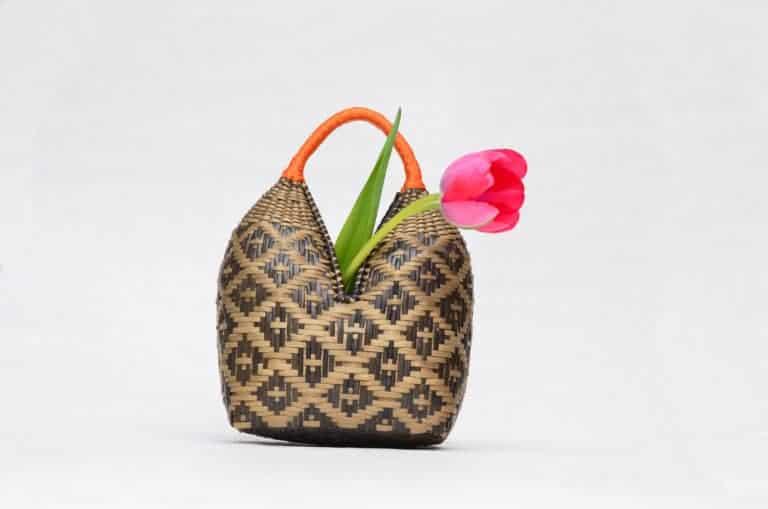 Picture of a Eperaara Siapidaara dos tetas basket hand woven in brown shrimp eyes pattern with golden orange handles holding a red tulip