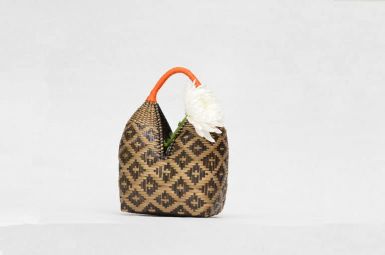 Picture of a dos tetas basket hand woven by the Eperaara Siapidaara tribe in brown shrimp eyes pattern with golden orange handles holding a white flower