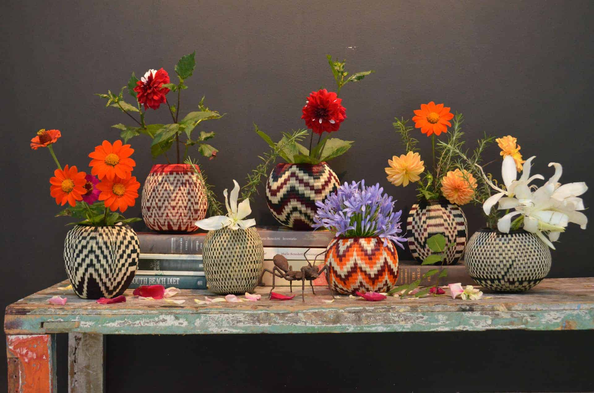 picture of various decorative vases woven from werregue natural fibers holding flowers on top of a shabby chic table which is also decorated with books and a metallic ant