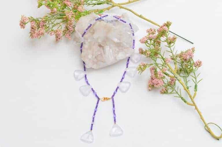 close up picture of an Amethyst Bead Necklace with Lavender Quartz Accents on white background decorated with flowers by Kiskadee Design