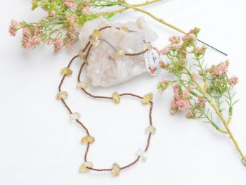 close up picture of a Long Dainty Raw Citrine Quartz Necklace on white background decorated with flowers by Kiskadee Design