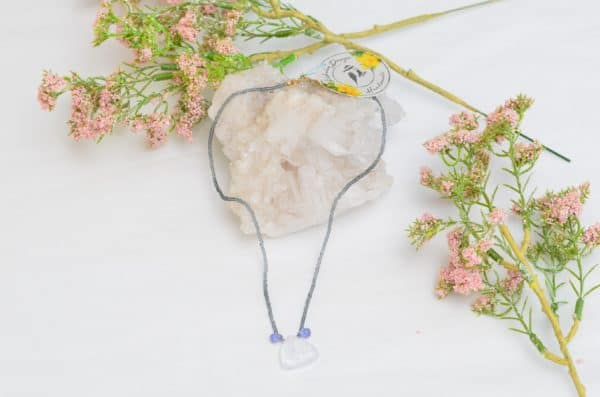 close up picture of a Quartz Pendant Necklace with Glass Beads and Faceted Amethyst Accent Drops on white background decorated with flowers by Kiskadee Design