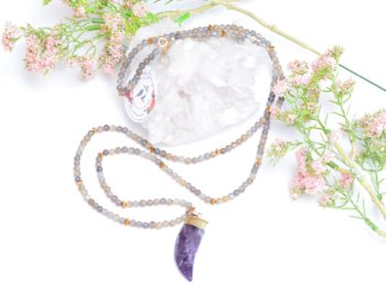close up picture of a Long Labradorite Bead Necklace with Amethyst Pendant on white background decorated with flowers by Kiskadee Design